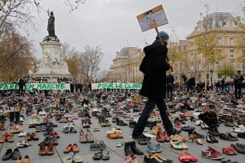 "A man walks between shoes as hundreds of pairs of shoes are displayed at the place de la Republique, in Paris, as part of a symbolic and peaceful rally called by the NGO Avaaz ""Paris sets off for climate"", Sunday, Nov. 29, 2015.  More than 140 world leaders are gathering around Paris for high-stakes climate talks that start Monday, and activists are holding marches and protests around the world to urge them to reach a strong agreement to slow global warming. (AP Photo/Laurent Cipriani)"