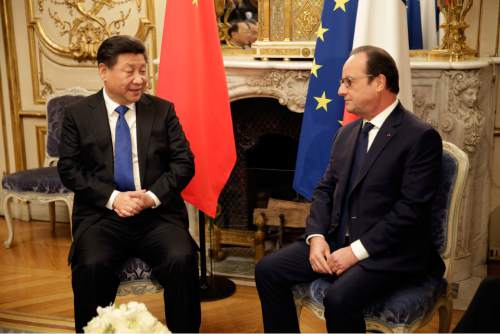 France's President Francois Hollande, right, meets with Chinese President Xi Jinping prior to a working dinner at the Elysee Palace in Paris, Sunday, Nov. 29, 2015. More than 140 world leaders are gathering around Paris for high-stakes climate talks that start Monday, and activists are holding marches and protests around the world to urge them to reach a strong agreement to slow global warming. (Philippe Wojazer/Pool Photo via AP)