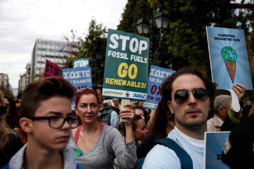 Protesters raise placards during the Global Climate March, a day ahead of the 2015 Paris Climate Change summit, in Athens, Sunday, Nov. 29, 2015. More than 140 world leaders are gathering around Paris for high-stakes climate talks that start Monday, and activists are holding marches and protests around the world to urge them to reach a strong agreement to slow global warming. (AP/Yorgos Karahalis)