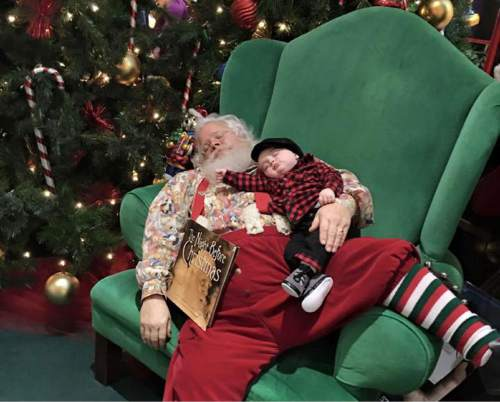 In this Nov. 25, 2015 photo provided by Donnie Walters, Walters' son Zeke snuggles up on Santa's lap during a visit to a shopping mall in Evansville, Ind.  Walters said his son fell asleep waiting in line and when they go to Santa, he asked him not to wake the boy. Santa leaned back in the big green chair with Zeke and a copy of The Night Before Christmas posing for a photo that makes it look like the pair fell asleep. (AP Photo via Donnie Walters)
