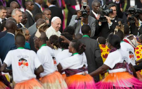 Pope Francis greets traditional dancers on his arrival at the airport in Nairobi, Kenya Wednesday, Nov. 25, 2015. Pope Francis left Wednesday for his first-ever visit to the continent, a whirlwind pilgrimage to Kenya, Uganda and the Central African Republic, bringing a message of peace and reconciliation to an Africa torn by extremist violence. (AP Photo/Ben Curtis)
