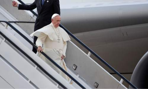 Pope Francis walks down the steps as he departs from his plane on his arrival at the airport in Nairobi, Kenya Wednesday, Nov. 25, 2015. Pope Francis left Wednesday for his first-ever visit to the continent, a whirlwind pilgrimage to Kenya, Uganda and the Central African Republic, bringing a message of peace and reconciliation to an Africa torn by extremist violence. (AP Photo/Ben Curtis)