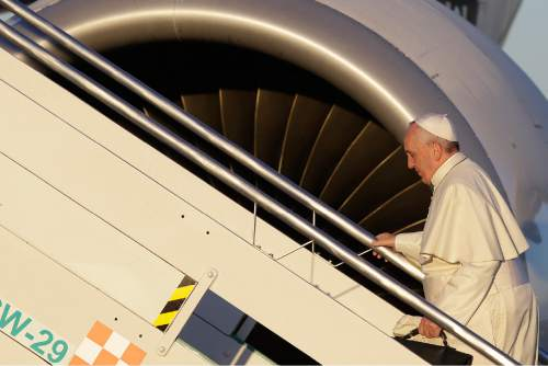 Pope Francis boards his airplane on the occasion of his trip to Africa, at Rome's Fiumicino International Airport, Wednesday, Nov. 25, 2015. Pope Francis is leaving for a trip that will take him to Kenya, Uganda and the Central African Republic, from Nov. 25-30. (AP Photo/Gregorio Borgia)