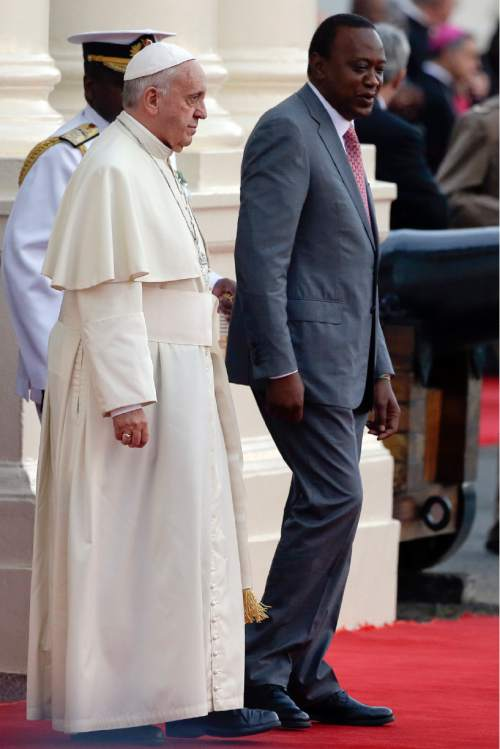 Pope Francis is greeted by Kenya's President Uhuru Kenyatta upon his arrival at Nairobi's State House, Wednesday, Nov. 25, 2015. Brushing aside concerns for his security, Pope Francis arrived in Kenya on Wednesday for his first-ever visit to Africa, including to Central African Republic, a country torn by fighting between Christian and Muslims. (AP Photo/Andrew Medichini)