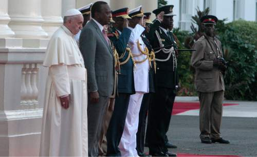 Pope Francis, left, flanked by Kenyan President Uhuru Kenyatta, second left, stand with senior Army Officers to review the honor guard at Nairobi State House, Kenya, Wednesday, Nov. 25, 2015. Pope Francis left Wednesday for his first-ever visit to the continent, a whirlwind pilgrimage to Kenya, Uganda and the Central African Republic, bringing a message of peace and reconciliation to an Africa torn by extremist violence . (AP Photo/Sayyid Azim)