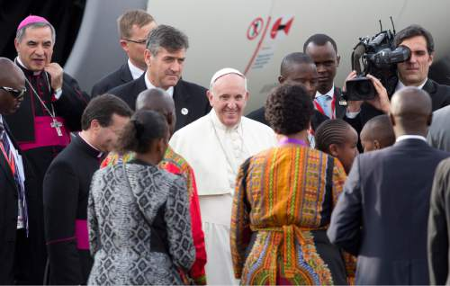 Pope Francis is greeted on his arrival at the airport in Nairobi, Kenya Wednesday, Nov. 25, 2015. Pope Francis left Wednesday for his first-ever visit to the continent, a whirlwind pilgrimage to Kenya, Uganda and the Central African Republic, bringing a message of peace and reconciliation to an Africa torn by extremist violence. (AP Photo/Ben Curtis)