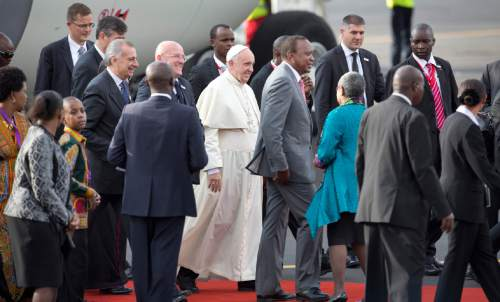 Pope Francis, center-left, walks with Kenya's President Uhuru Kenyatta, center-right, on his arrival at the airport in Nairobi, Kenya Wednesday, Nov. 25, 2015. Pope Francis left Wednesday for his first-ever visit to the continent, a whirlwind pilgrimage to Kenya, Uganda and the Central African Republic, bringing a message of peace and reconciliation to an Africa torn by extremist violence. (AP Photo/Ben Curtis)