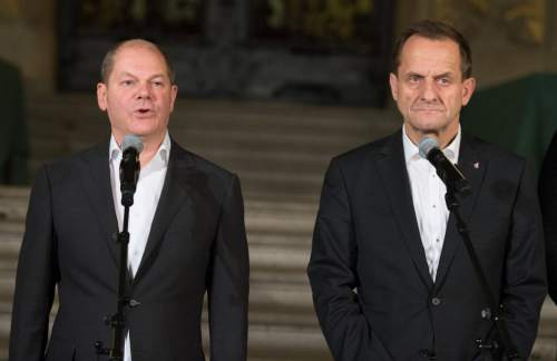 In this Nov. 29, 2015 photo Hamburg mayor Olaf Scholz, left, and Alfons Hoermann, president of the German Olympic committee, give a press statement in the Hamburg, northern Germany, city hall after people voted against the city running for hosting the 2014 Summer Olympics. (Daniel Reinhardt/dpa via AP)