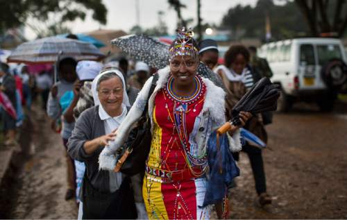 A Catholic sister and a Maasai woman arrive just after dawn in the rain and mud to attend a Mass to be given by Pope Francis at the campus of the University of Nairobi in Kenya Thursday, Nov. 26, 2015. Pope Francis is in Kenya on his first-ever trip to Africa, a six-day pilgrimage that will also take him to Uganda and the Central African Republic. (AP Photo/Ben Curtis)