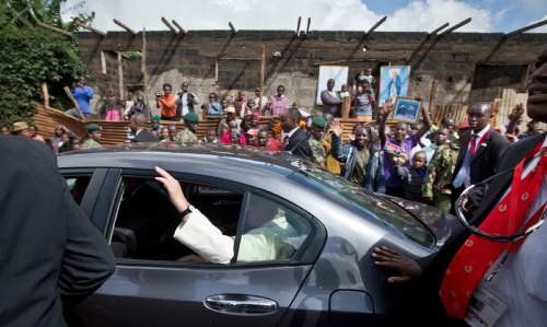 Pope Francis waves to local residents as he leaves in a saloon car after visiting St. Joseph The Worker Catholic Church in the Kangemi slum of Nairobi, Kenya Friday, Nov. 27, 2015. Pope Francis is in Kenya on his first-ever trip to Africa, a six-day pilgrimage that will also take him to Uganda and the Central African Republic. (AP Photo/Ben Curtis)
