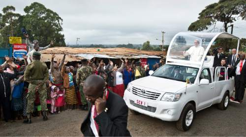 Local residents wave at Pope Francis as he drives to St. Joseph The Worker Catholic Church in the Kangemi slum of Nairobi, Kenya Friday, Nov. 27, 2015. Pope Francis is in Kenya on his first-ever trip to Africa, a six-day pilgrimage that will also take him to Uganda and the Central African Republic. (AP Photo/Ben Curtis)