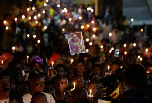 People hold candles as they wait for the arrival of Pope Francis for a meeting with catechists and teachers during his visit to Munyonyo, Uganda, Friday, Nov. 27, 2015. Pope Francis is in Africa for a six-day visit that is taking him to Kenya, Uganda and the Central African Republic. (AP Photo/Andrew Medichini)
