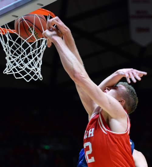 Steve Griffin  |  The Salt Lake Tribune  Utah Utes forward Jakob Poeltl (42) gets smacked across the face by Brigham Young Cougars forward Kyle Davis (21) as he slams home two during first half action in the Utah versus BYU men's basketball game at the Huntsman Center in Salt Lake City, Wednesday, December 2, 2015.