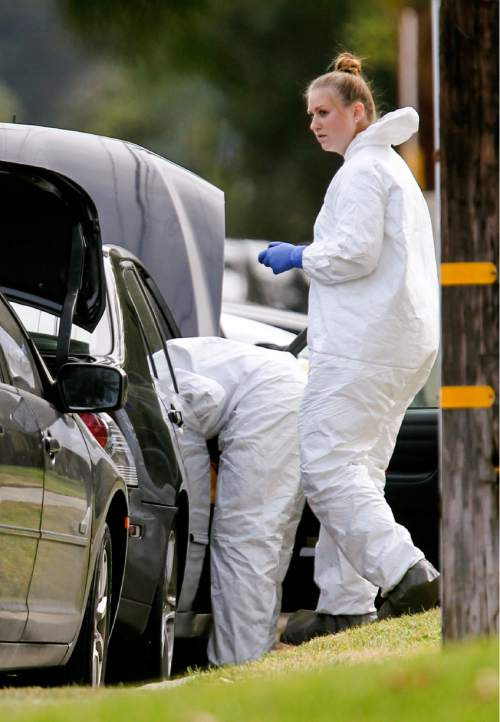 FBI agents investigate a car near a home in connection to the shootings in San Bernardino, Thursday, Dec. 3, 2015, in Redlands, Calif. A heavily armed man and woman opened fire Wednesday on a holiday banquet for his co-workers, killing multiple people and seriously wounding others in a precision assault, authorities said. Hours later, they died in a shootout with police. (AP Photo/Ringo H.W. Chiu)