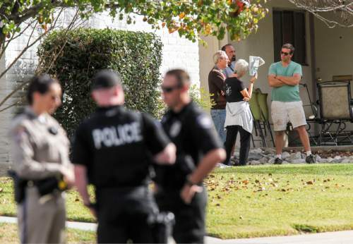 People gather in the neighborhood near the home in connection to the shootings in San Bernardino, Thursday, Dec. 3, 2015, in Redlands, Calif.. A heavily armed man and woman opened fire Wednesday on a holiday banquet for his co-workers, killing multiple people and seriously wounding others in a precision assault, authorities said. Hours later, they died in a shootout with police. (AP Photo/Ringo H.W. Chiu)