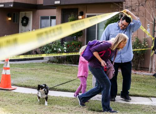People leave their home in the neighborhood near a home being investigated in connection to the shootings in San Bernardino, Thursday, Dec. 3, 2015, in Redlands, Calif. A heavily armed man and woman opened fire Wednesday on a holiday banquet for his co-workers, killing multiple people and seriously wounding others in a precision assault, authorities said. Hours later, they died in a shootout with police. (AP Photo/Ringo H.W. Chiu)
