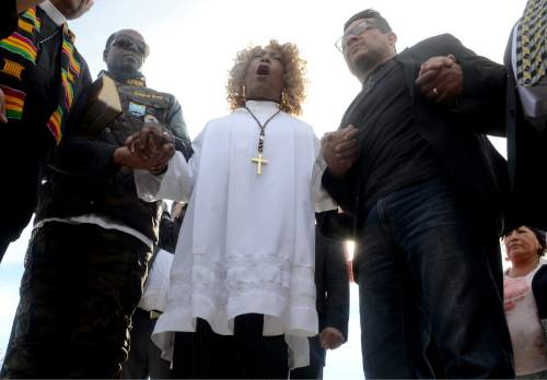 Dr. Jeannetta Million, center, of Victorious Believers Church leads a group of local pastors in a brief prayer vigil on Thursday December, 2015 at the corner of Waterman and Orange Show Drive in San Bernardino Calif. just blocks from the scene of a mass shooting. A heavily armed husband and wife dressed for battle opened fire on a holiday banquet for his co-workers Wednesday, killing multiple people and seriously wounding others in a precision assault, authorities said. Hours later, they died in a shootout with police.  (James Quigg/Daily Press via AP)