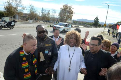 Dr. Jeannetta Million of Victorious Believers Church, center, leads a group of local pastors in a brief prayer vigil on Thursday Dec. 3, 2015, at the corner of Waterman and Orange Show Drive in San Bernardino Calif. just blocks from the scene of a mass shooting. A heavily armed husband and wife dressed for battle opened fire on a holiday banquet for his co-workers Wednesday, killing multiple people and seriously wounding others in a precision assault, authorities said. Hours later, they died in a shootout with police. (James Quigg/Daily Press via AP)