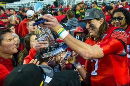 Chris Detrick  |  The Salt Lake Tribune Utah Utes quarterback Travis Wilson (7) hands off his  MVP trophy after winning the Royal Purple Las Vegas Bowl at Sam Boyd Stadium Saturday December 20, 2014. Utah defeated Colorado State 45-10.