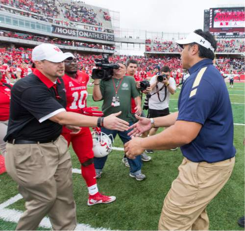 Houston's head coach Tom Herman and Navy's head coach Ken Niumatalolo shaking hands on the field after an NCAA college football game Friday, Nov. 27, 2015, in Houston, Texas. Houston defeated Navy 52-31. (AP Photo/Juan DeLeon)