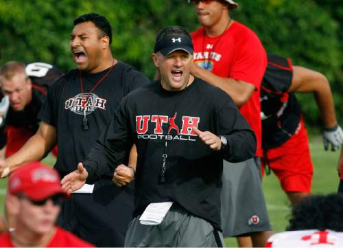 UTAH FOOTBALL  Utah head coach Kyle Whittingham (center) and defensive coordinator Kalani Sitake (left) yell as they have the team break up into smaller units to begin drills, Thursday, 8/06/09. Scott Sommerdorf  / The Salt Lake Tribune