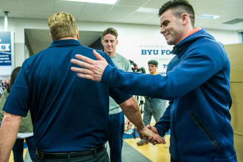 Chris Detrick  |  The Salt Lake Tribune Tanner Mangum greets Cougar football head coach Bronco Mendenhall as he walks away after a press conference at Brigham Young University Friday December 4, 2015.  Mendenhall signed a five-year contract with the University of Virginia that will pay him $3.25 million annually, estimated to be more than three times the money he makes coaching BYU.