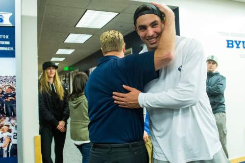 Chris Detrick     The Salt Lake Tribune Bronson Kaufusi hugs Cougar football head coach Bronco Mendenhall as he walks away after a press conference at Brigham Young University Friday December 4, 2015.  Mendenhall signed a five-year contract with the University of Virginia that will pay him $3.25 million annually, estimated to be more than three times the money he makes coaching BYU.