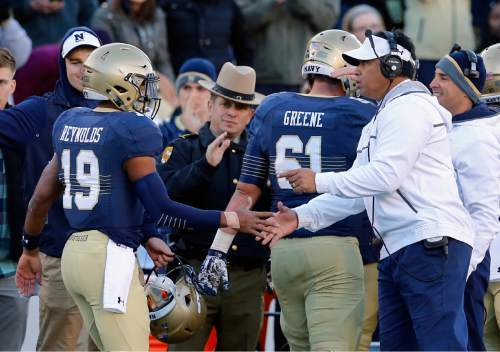 Navy head coach Ken Niumatalolo, right, greets quarterback Keenan Reynolds (19) after Reynolds scored a touchdown to break the NCAA all-time rushing touchdown record in the first half of an NCAA college football game against SMU, Saturday, Nov. 14, 2015, in Annapolis, Md. (AP Photo/Patrick Semansky)