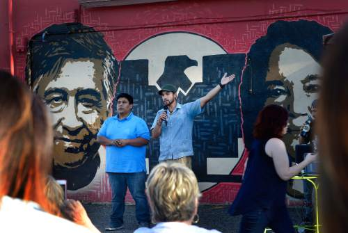Scott Sommerdorf   |  The Salt Lake Tribune Miguel Dominguez, left, owner of the Azteca De Oro Taqueria restaurant and artist Miguel Galaz speaks to the crowd during the vigil to save the mural of Cesar Chavez and Dolores Huerta on its north wall. The City of West Jordan is trying to get that restaurant to paint over or downsize the mural, saying it violates the city sign ordinance, Thursday, July 23, 2015.