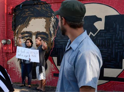 "Scott Sommerdorf   |  The Salt Lake Tribune Artist Miguel Galaz, right, turns to see Raymi Gutierrez and James Lemisio raise their hands in support of the mural of Cesar Chavez and Dolores Huerta at the Azteca De Oro Taqueria restaurant, Thursday, July 23, 2015. The pair are holding signs that say ""#Art is not a sign"" and ""#Keep our Murals""."