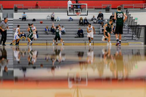 Trent Nelson  |  The Salt Lake Tribune Reflections on the court as Bingham plays Olympus in the first round of the boys' basketball Elite 8 Tournament at American Fork High School, Thursday December 10, 2015.