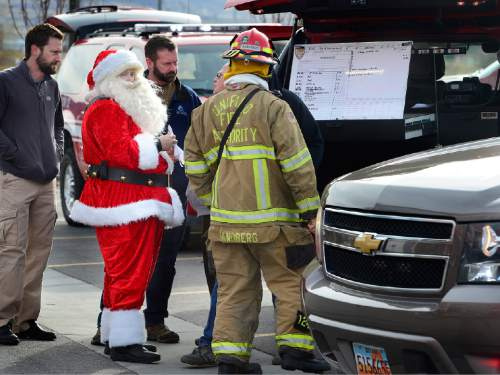 Scott Sommerdorf   |  The Salt Lake Tribune UFA fire investigator Don Buckley - in the Santa suit - works with other investigators to try to pinpoint the source of the two-alarm fire at the Loveland Living Aquarium in Draper, Sunday, December 13, 2015. Buckley happened to be at the aquarium with his with Judy (Mrs. Claus), meeting with children when the fire started. The fire was limited to the rooftop, and no animals were affected in the aquarium.