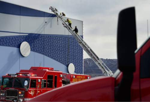 Scott Sommerdorf   |  The Salt Lake Tribune UFA firefighters scale a ladder on their way to the roof to investigate a two-alarm fire at the Loveland Living Aquarium in Draper, Sunday, December 13, 2015. The fire was limited to the rooftop, and no animals were affected in the aquarium.