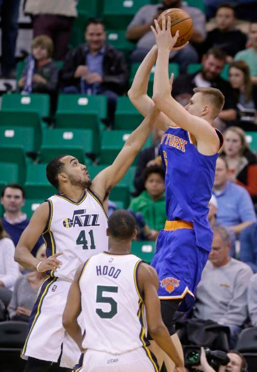 New York Knicks forward Kristaps Porzingis, right, shoots as Utah Jazz's Trey Lyles (41) defends and Rodney Hood (5) looks on during the first quarter of an NBA basketball game Wednesday, Dec. 9, 2015, in Salt Lake City. (AP Photo/Rick Bowmer)