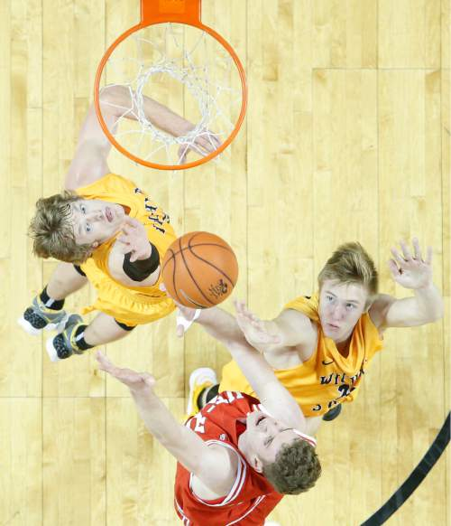 Wichita State guard Ron Baker, left, and Rauno Nurger defend against Utah forward Jakob Poeltl, bottom, during the second half of an NCAA college basketball game, Saturday, Dec. 12, 2015 in Wichita, Kan. (Travis Heying/The Wichita Eagle via AP) LOCAL TELEVISION OUT; MAGS OUT; LOCAL RADIO OUT; LOCAL INTERNET OUT; MANDATORY CREDIT