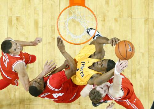 Wichita State forward Rashard Kelly, center, goes to the basket against Utah forward Jakob Poeltl, bottom right, Dakarai Tucker  and  Brekkott Chapman, left, during the first half of an NCAA college basketball game, Saturday, Dec. 12, 2015 in Wichita, Kan. (Travis Heying/The Wichita Eagle via AP) LOCAL TELEVISION OUT; MAGS OUT; LOCAL RADIO OUT; LOCAL INTERNET OUT; MANDATORY CREDIT
