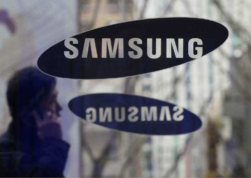 FILE - In this Dec. 12, 2013 file photo, a man passes by the Samsung Electronics Co. logos at its headquarters in Seoul, South Korea. In a patent fight with Apple, Samsung is asking the Supreme Court to take a digital-age look at a type of dispute it last confronted in the horse-and-buggy era. South Korea-based Samsung on Monday appealed a $399 million judgment for illegally copying patented aspects of the look of Apple's iPhone, the latest round in a long-running fight between the two tech industry giants. (AP Photo/Ahn Young-joon, File)