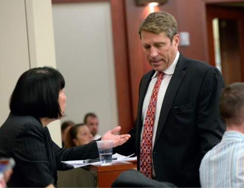 Al Hartmann  |  The Salt Lake Tribune Deputy Salt Lake County Attorney  Chou Chou Collins, left, huddles with defense lawyer Scott Williams prior to a status hearing for former Utah Attorney General John Swallow in Third Distrcit Court in Salt Lake City Monday Dec. 14. Williams who has recently taken the case asked Judge Elizabeth Hruby-Mills for more time to prepare his defense for Swallow has pleaded not guilty to 14 felony and misdemeanor charges in connection with a bribery and corruption scandal stemming from his time in the attorney general's office.  Swallow did not appear in court due to Monday's snow storm.