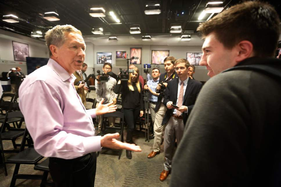 Republican presidential candidate, Ohio Gov. John Kasich talks with voters during a campaign stop with young professions, Thursday, Dec. 10, 2015, in Manchester, N.H. (AP Photo/Jim Cole)