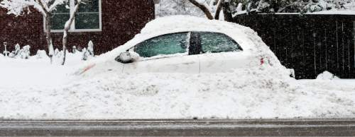Steve Griffin  |  The Salt Lake Tribune  Snow covers a compact car in Salt Lake City as a major storm dumped snow through out the sate Monday, December 14, 2015.