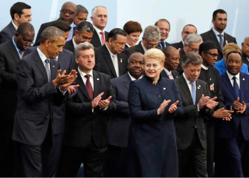 U.S. President Barack Obama, left, and Brazil's President Dilma Rousseff, front row third from right, applaud as they pose with world leaders for a group photo at the COP21, United Nations Climate Change Conference, in Le Bourget, outside Paris, Monday, Nov. 30, 2015. (AP Photo/Jacky Naegelen, Pool)