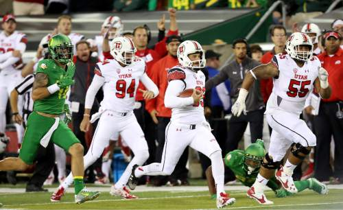 Utah punter Tom Hackett (33) runs the ball after a fake punt during the second half of an NCAA college football game against Oregon, Saturday, Sept. 26, 2015, in Eugene, Ore. (AP Photo/Ryan Kang)