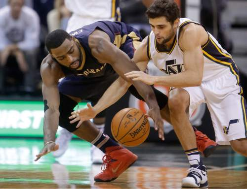 Utah Jazz guard Raul Neto, right, and New Orleans Pelicans guard Tyreke Evans, left, scramble for the ball during the second half of an NBA basketball game Wednesday, Dec. 16, 2015, in Salt Lake City. The Pelicans won 104-94. (AP Photo/Rick Bowmer)