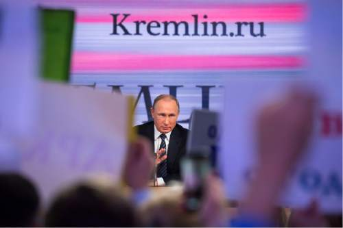 Russian President Vladimir Putin speaks at his annual end of year news conference as reporters hold up posters to attract his attention, in Moscow, Russia, Thursday, Dec. 17, 2015. President Vladimir Putin said Thursday Russia is ready to improve ties with the United States and work with whomever is elected its next president. (AP Photo/Alexander Zemlianichenko)