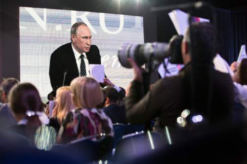 Russian President Vladimir Putin speaking at his annual end of year news conference is projected on a screen as reporters hold up posters to attract his attention, in Moscow, Russia, Thursday, Dec. 17, 2015. President Vladimir Putin said Thursday Russia is ready to improve ties with the United States and work with whomever is elected its next president. (AP Photo/Alexander Zemlianichenko)