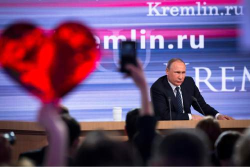Russian President Vladimir Putin speaks at his annual end of year news conference as  a reporter holds up a heart-shaped poster to attract his attention, in Moscow, Russia, Thursday, Dec. 17, 2015. President Vladimir Putin said Thursday Russia is ready to improve ties with the United States and work with whomever is elected its next president. (AP Photo/Alexander Zemlianichenko)