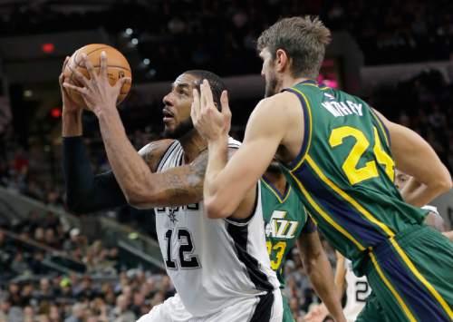 San Antonio Spurs forward LaMarcus Aldridge (12) shoots past Utah Jazz center Jeff Withey (24) during the first half of an NBA basketball game, Monday, Dec. 14, 2015, in San Antonio. (AP Photo/Eric Gay)