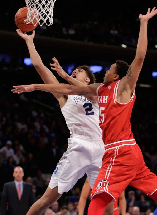 Duke forward Chase Jeter (2) puts up a shot against Utah guard Lorenzo Bonam (15) during the first half of an NCAA college basketball game, Saturday, Dec. 19, 2015, in New York. (AP Photo/Julie Jacobson)