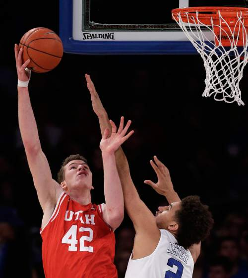 Utah forward Jakob Poeltl (42) puts up a shot against Duke forward Chase Jeter (2) during the first half of an NCAA college basketball game, Saturday, Dec. 19, 2015, in New York. (AP Photo/Julie Jacobson)