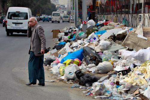 In this Thursday, Dec. 17, 2015 photo, a Lebanese man covers his nose from the smell as he passes by a pile of garbage on a street in Beirut, Lebanon. Lebanon's trash collection crisis which set off summer protests is entering its sixth month, but you would hardly be able to know it in Beirut. (AP Photo/Bilal Hussein)